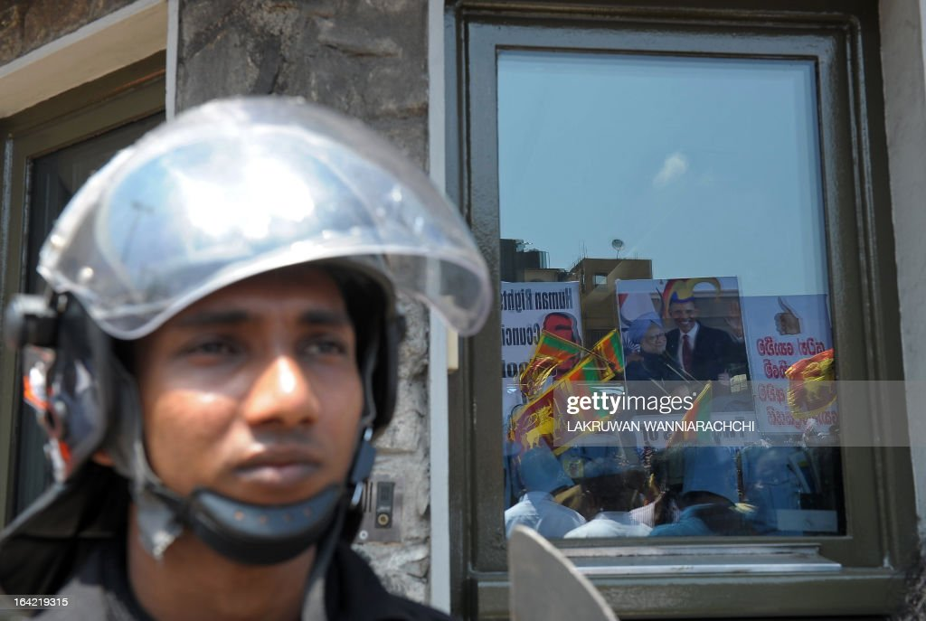 Pro-government activists are reflected in the glass of the US embassy during a protest in Colombo on March 21, 2013, as the UN Human Rights Council in Geneva was set to vote on a resolution pressing for a war crimes probe against Sri Lanka. Hundreds of demonstrators held up traffic outside the US embassy, close to Sri Lankan President Mahinda Rajapakse's official residence, and chanted slogans denouncing US President Barack Obama and India's Prime Minister Manmohan Singh.