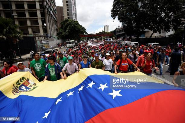Progovernment activists hold a large Venezuelan Flag during a rally to support Venezuelan President Nicolas Maduro and oppose US President Donald...