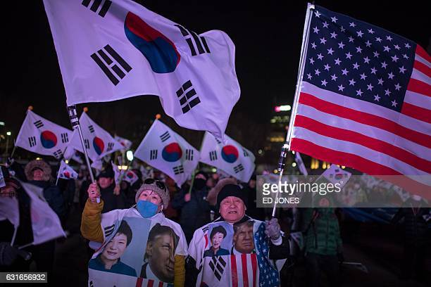 Progovernment activists wearing clothes showing images of US presidentelect Donald Trump and South Korea's President Park GeunHye take part in a...
