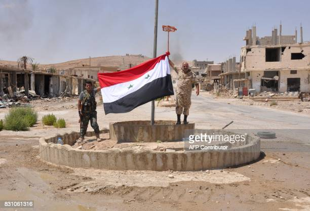 Progovernment fighters hold up a Syrian flag in the central Syrian town of AlSukhnah situated in the county's large desert area called the Badiya on...