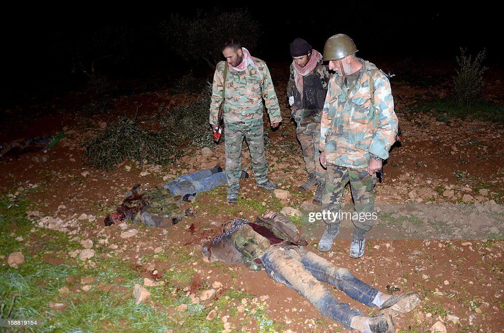 Pro-government fighters inspect the bodies of rebels killed during clashes at the Air Defence Base in Tal Hassil 15 kms from Aleppo Airport on December 30, 2012. International envoy Lakhdar Brahimi warned the Syrian war was worsening 'by the day' as he announced a peace plan he believed could find support from world powers, including key Syria ally Russia. AFP PHOTO / STR
