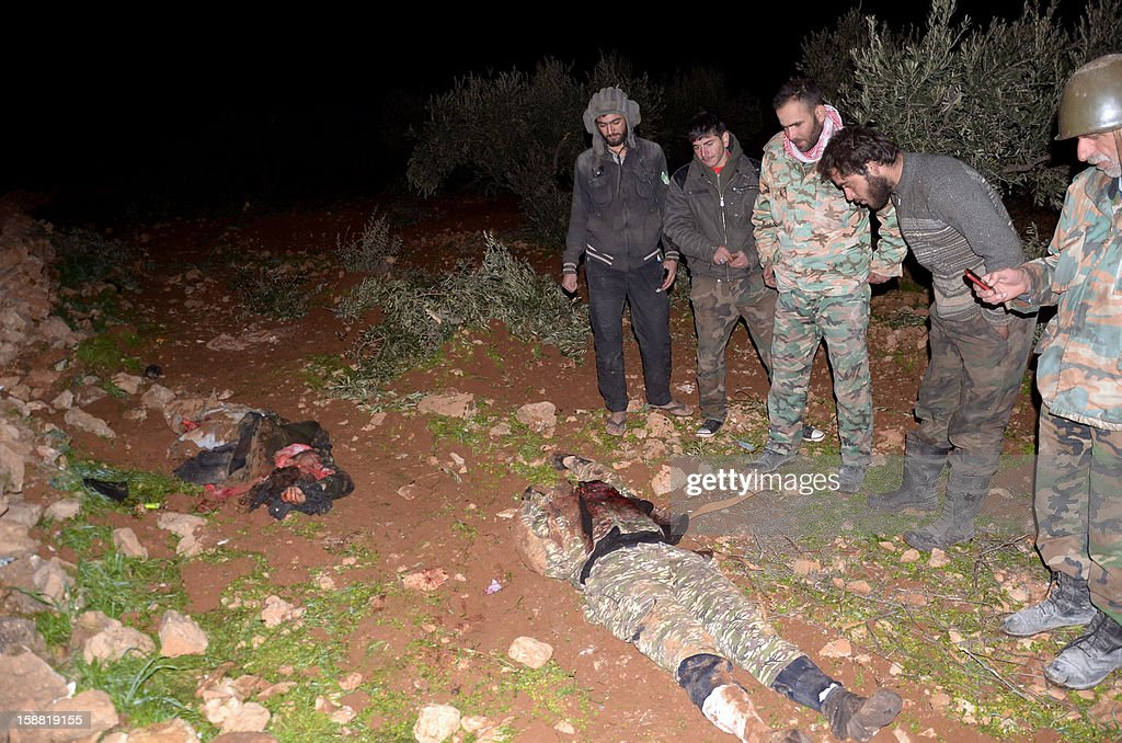 Pro-government fighters inspect the bodies of rebels killed during clashes at the Air Defence Base in Tal Hassil 15 kms from Aleppo Airport on December 30, 2012. International envoy Lakhdar Brahimi warned the Syrian war was worsening 'by the day' as he announced a peace plan he believed could find support from world powers, including key Syria ally Russia.
