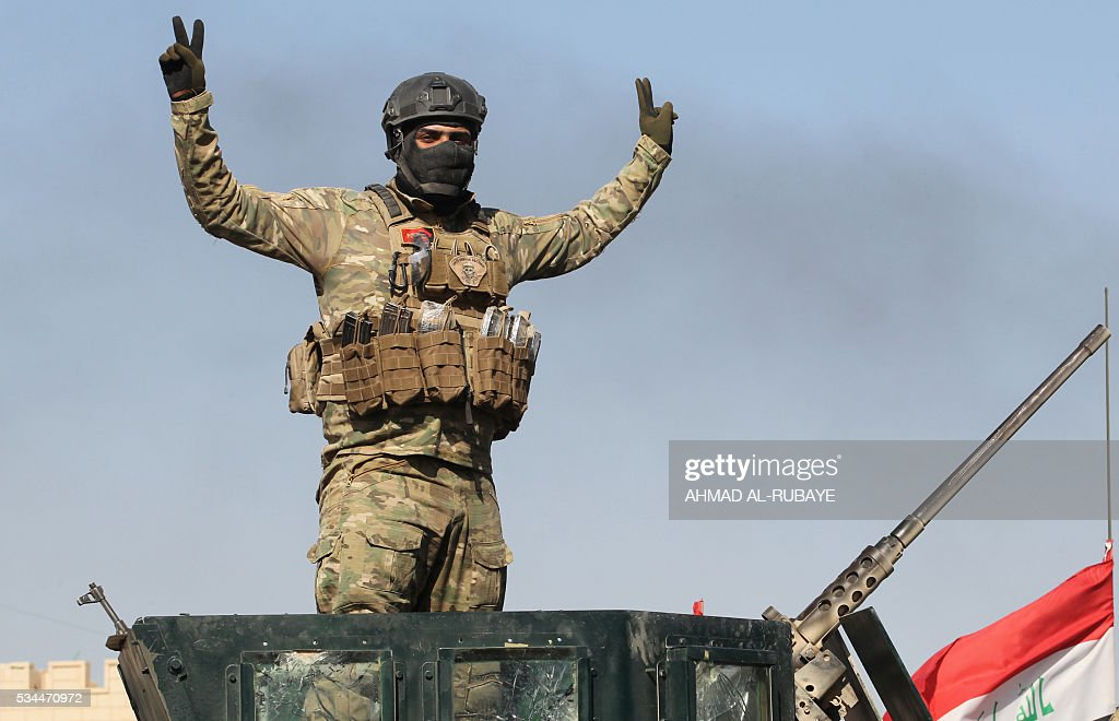 A pro-government forces fighter flashes the sign for victory near al-Sejar village, north-east of Fallujah, on May 26, 2016, as they take part in a major assault to retake the city from the Islamic State (IS) group. Tens of thousands of security forces are deployed in the Fallujah area for an assault aimed at retaking the city from the Islamic State group. Fallujah, which lies only 50 kilometres (30 miles) west of Baghdad, has been out of government control since January 2014 and is one of only two remaining major Iraqi cities still in IS hands, the other being Mosul. / AFP / AHMAD