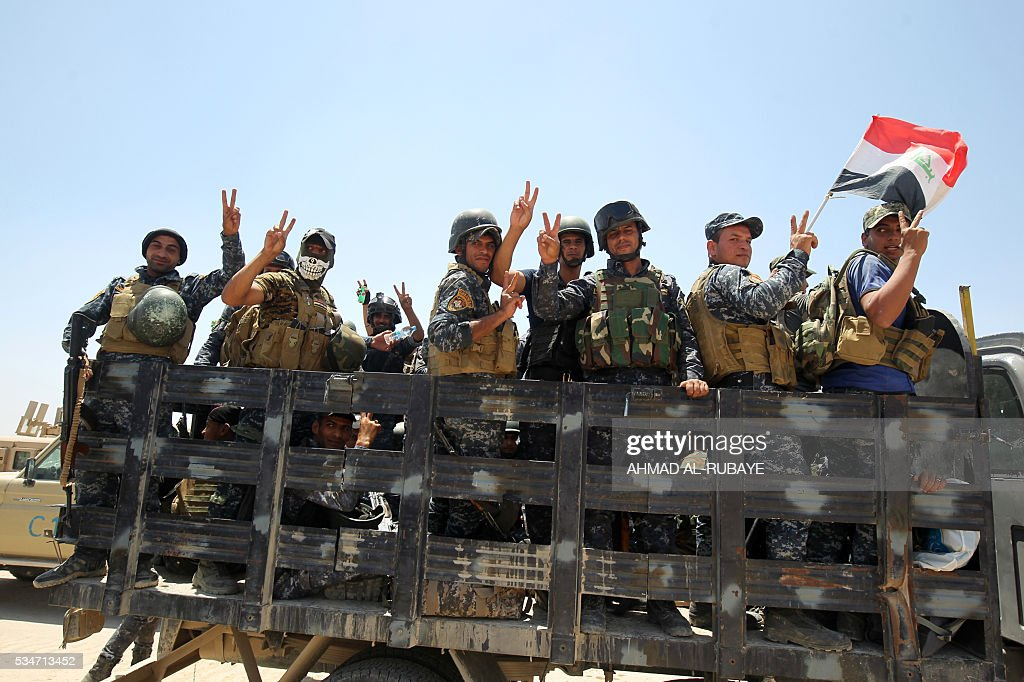 Pro-government forces fighters celebrate in the al-Sejar village, in Iraq's Anbar province, on May 27, 2016, as they take part in a major assault to retake the city of Fallujah, from the Islamic State (IS) group. Hundreds of people fled the Fallujah area with the help of Iraqi forces who are fighting to retake the city from the Islamic State jihadist group, officials said. Iraqi forces launched an operation to recapture Fallujah, an IS stronghold located just 50 kilometres (30 miles) west of Baghdad, at the start of this week. RUBAYE