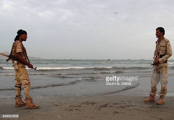 Progovernment forces soldiers stand on the beach in the southern coastal city of Aden as Yemeni coast guards search for the remains of a United Arab...
