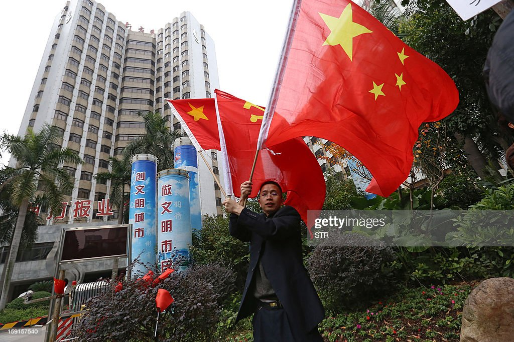 A pro-government protester holds Chinese flags outside the headquarters of Nanfang Media Group in Guangzhou on January 9, 2013. A Chinese weekly newspaper at the centre of rare public protests about government censorship will publish as usual on January 10, a senior reporter said, following reports of a deal to end the row. The row at the popular liberal paper, which had an article urging greater rights protection replaced with one praising the ruling communist party, has seen demonstrators mass outside its headquarters in the southern city of Guangzhou.