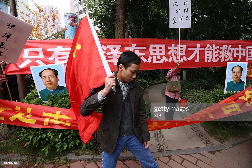 Pro-government protesters hold flags, banners and portraits of late Chinese chairman Mao Zedong outside the headquarters of Nanfang Media Group in Guangzhou on January 9, 2013. A Chinese weekly newspaper at the centre of rare public protests about government censorship will publish as usual on January 10, a senior reporter said, following reports of a deal to end the row. The row at the popular liberal paper, which had an article urging greater rights protection replaced with one praising the ruling communist party, has seen demonstrators mass outside its headquarters in the southern city of Guangzhou.