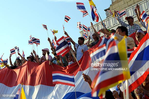 Progovernment protesters wave national flags and pictures showing Thai King Bhumibol Adulyadej and Queen Sirikit during a counterprotest at Victory...