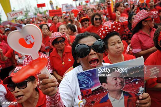 Progovernment red shirt supporter holding a picture of former Prime Minister Thaksin Shinawatra reacts to a speech during a large rally on the...