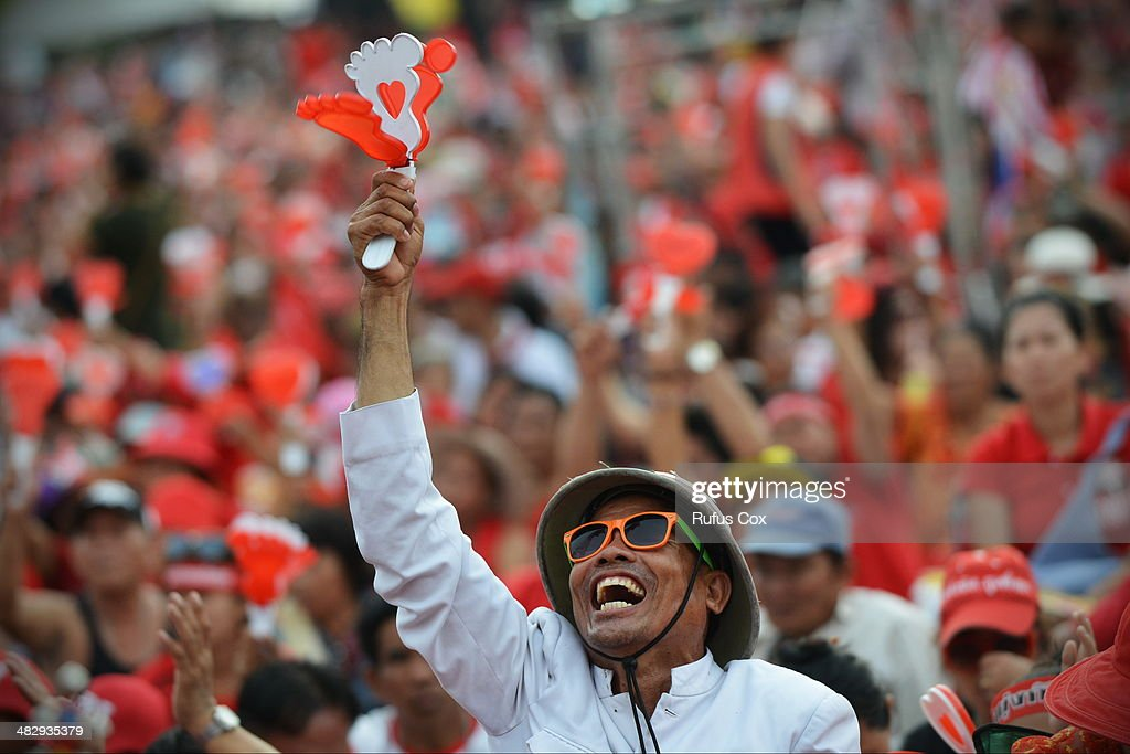 Pro-government red shirt supporters react to a speech during a large rally on the outskirts of the Thai capital on April 5, 2014 in Bangkok, Thailand. Tens of thousands of government supporters from across the country massed on the western suburbs of Bangkok in a show of strength, warning that any opposition attempt to remove the embattled caretaker administration of Prime Minister Yingluck Shinawatra would be met with resistance.