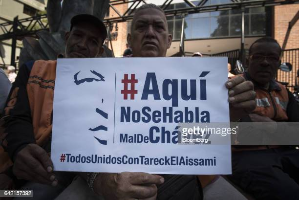 A progovernment supporters hold up signs that read 'Here We Do Not Speak Badly Of Chavez All United With Tareck El Aissami' during a protest against...