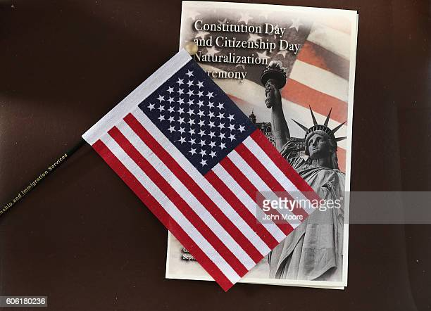 A program and US flag sit out before a naturalization ceremony on Ellis Island on September 16 2016 in New York City The ceremony marked US...