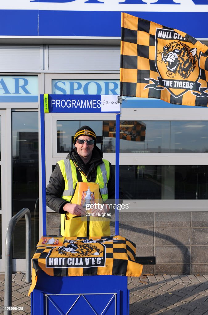A programme seller poses outside the K C Stadium prior the FA Cup with Budweiser Third Round match between Hull City and Leyton Orient at the KC Stadium on January 5, 2013 in Hull, England.