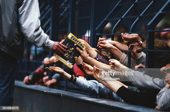 A programme seller sells match day programmes through the safety fences during the First Division match between Everton and Manchester United at...