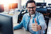 Young smiling handsome IT expert giving thumb up