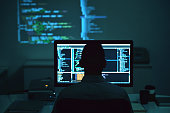 Rear view of programmer working on new project in dark office