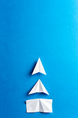 Progress concept. Development attainment, motivation, growth concept. Business concept of goals, success, achievement and challenge. White paper airplanes under construction on blue background.
