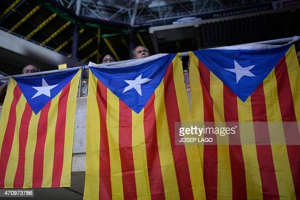 Proindependence Catalans sit behind Catalan flags during an event organised by the Catalan independence movement at the Palau Sant Jordi built for...