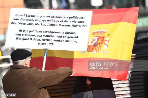 A Proindependence protestor holding a sign reading 'Political prisonners in Europe dictatorship mafia country and violence what do you do Merkel...