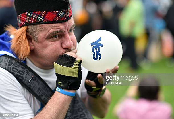 A proindependence supporter blows a 'Yes' balloon during a rally in Glasgow's George Square in Scotland on September 17 ahead of the referendum on...