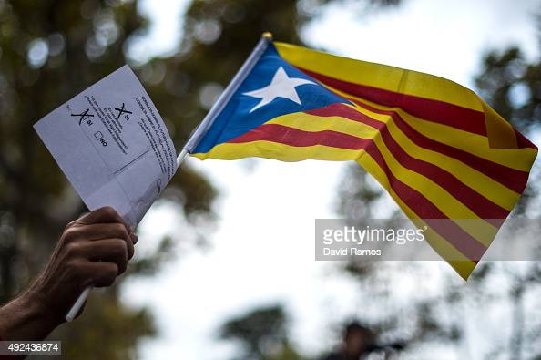 ProIndependence supporter holds up a ballot paper used in the unofficial referendum of last November 9 and a ProIndependence Catalan flag as he...