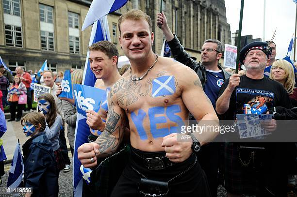 A proindependence supporter with a Saltire flag and a 'Yes' written on his body joins a march and rally in Edinburgh on September 21 2013 in support...