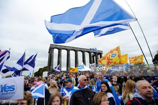 Proindependence supporters wave the Saltire as they gather in Edinburgh on September 21 2013 for a march and rally in support of a yes vote in the...
