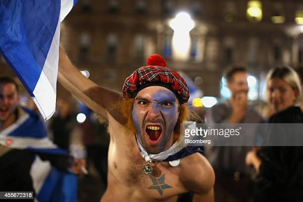A proindependence 'yes' campaign supporters waves a St Andrew's or Saltire flag the national flag of Scotland during a demonstration at George square...