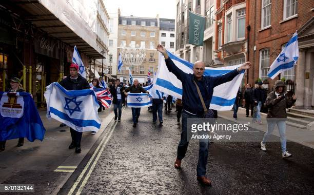 ProIsrael group hold Israeli flags as proPalestinian supporters hold a national march through central London England on November 4 demanding justice...
