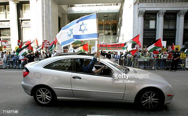 ProIsraeli demonstrators wave flags from a car in support of Israel's military offensive against Palestine and Lebanon as they drive by a group of...