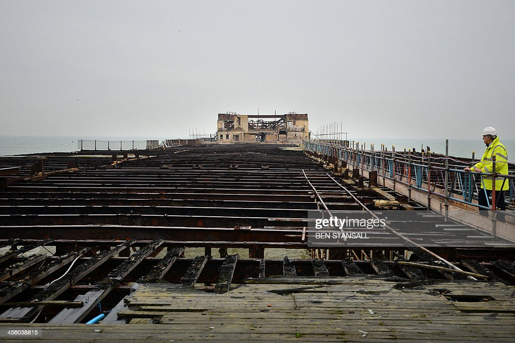 Project manager David Spooner surveys the burnt-out remains of Hastings Pier in Hastings, southern England, on December 13, 2013 ahead of the start of a multi-million pound regeneration project. Hastings Pier was originally constructed in opulent style in the late 19th century seeing its heyday in the 1930s and hosting music concerts by major artists including The Rolling Stones in the 1960s and 70s. After undergoing various additions and re-construction to repair storm and fire damage throughout the 20th century the Victorian pier finally suffered a devastating fire in 2010 which destroyed much of the superstructure leaving just a burnt out shell. Following a Heritage Lottery Fund (HLF) grant and money from other funds a 14 million GBP regeneration project is set to begin work on January 6, 2014.