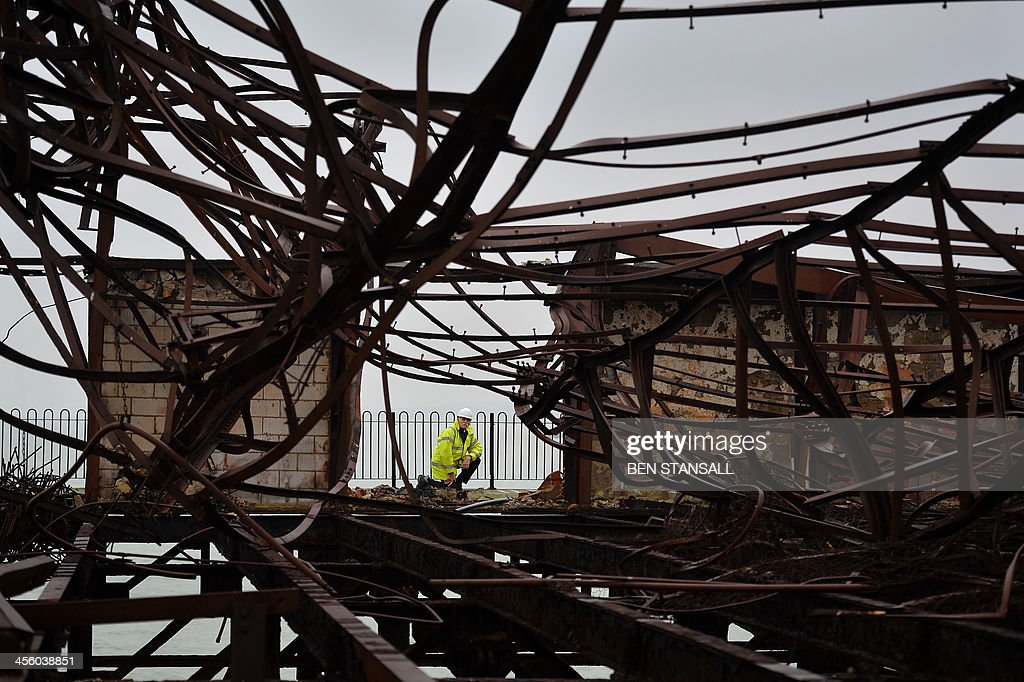 Project manager David Spooner surveys the tangled burnt-out remains of the ballroom on Hastings Pier in Hastings, southern England, on December 13, 2013 ahead of the start of a multi-million pound regeneration project. Hastings Pier was originally constructed in opulent style in the late 19th century seeing its heyday in the 1930s and hosting music concerts by major artists including The Rolling Stones in the 1960s and 70s. After undergoing various additions and re-construction to repair storm and fire damage throughout the 20th century the Victorian pier finally suffered a devastating fire in 2010 which destroyed much of the superstructure leaving just a burnt out shell. Following a Heritage Lottery Fund (HLF) grant and money from other funds a 14 million GBP regeneration project is set to begin work on January 6, 2014.