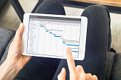 Project manager working with Gantt chart with planning software on digital tablet computer to update the schedule and deadlines