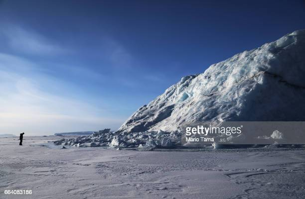 NASA project scientist Nathan Kurtz surveys an iceberg locked in sea ice near Thule Air Base on March 26 2017 in Pituffik Greenland NASA's Operation...