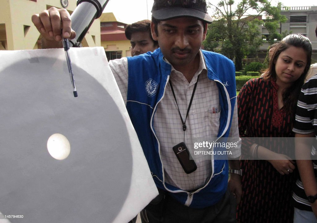 A projected image from a telescope of Planet Venus in transit across the Sun is pictured on a screen as skygazers watch the celestial event using protective eyewear in Siliguri on June 6, 2012. Astronomers around the world trained their telescopes on the skies to watch Venus pass in front of the Sun, a once-in-a-lifetime event that will not be seen for another 105 years. AFP PHOTO/Diptendu DUTTA