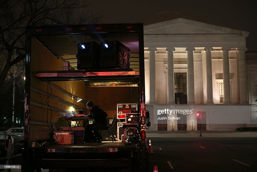 A projectionist sits in a truck as images and quotes by Chinese artist and activist Ai Weiwei are projected on a 74-foot-tall marble First Amendment tablet on the exterior of the Newseum on January 17, 2013 in Washington, DC. The exhibit runs 7 p.m. each night through January 17.