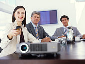 Projector on table, businesswoman using remote