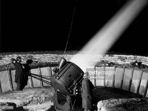 A projector operating from its sunken sandbagged emplacement at a searchlight station in the London area