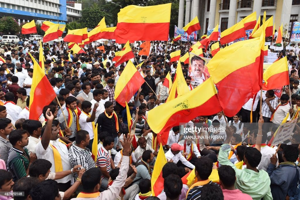 Pro-Kannada activists wave the Karnataka flag stage during a demonstration calling for the shutdown of the city in protest against the rising crimes against women and children in Bangalore on July 31, 2014. About 50-pro-Kannada organisations took out a protest rally from Town Hall to the state secretariat in the city centre and submitted a memorandum to Karnataka Chief Minister Siddaramaiah to check crimes against women and urging him to take stringent action against the perpetrators. AFP PHOTO/Manjunath KIRAN