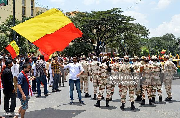 A proKarnataka activist waves the Karnataka flag over police personnelduring a statewide strike in Bangalore on September 9 2016 Agitation in the...