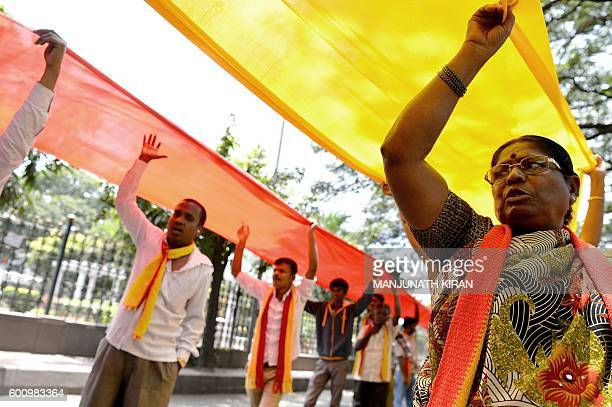 ProKarnataka activists carry a large Karnataka flag while they participate in a rally during a statewide strike in Bangalore on September 9 2016...
