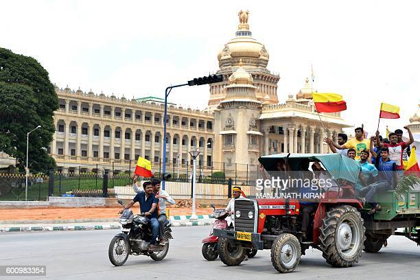 ProKarnataka activists wave the Karnataka flag while they participate in a rally during a statewide strike in Bangalore on September 9 2016 Agitation...
