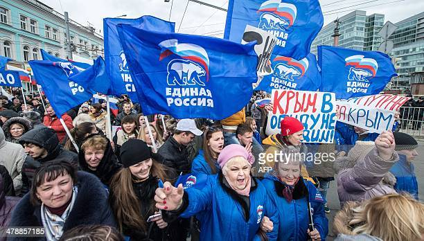ProKremlin activists carry flags of of the ruling party United Russia as they march in Moscow on March 15 during a rally in support of recent...