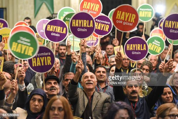 ProKurdish Peoples' Democratic Party party supporters hold signs during a press conference to launch the party's 'no' campaign in Istanbul on March 2...