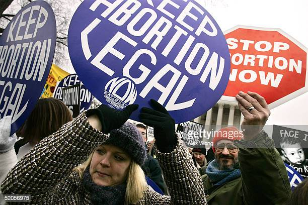 Prolife activist Bill Rosanelli of Montague New Jersey and local prochoice activist Leanne Libert hold signs outside the US Supreme Court during the...