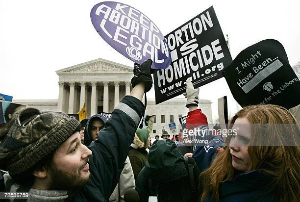 Prolife activist Jessica Meunier of Fitchburg MA and proabortion activist Luqman Clark of Arlington VA hold up signs as they protest outside US...