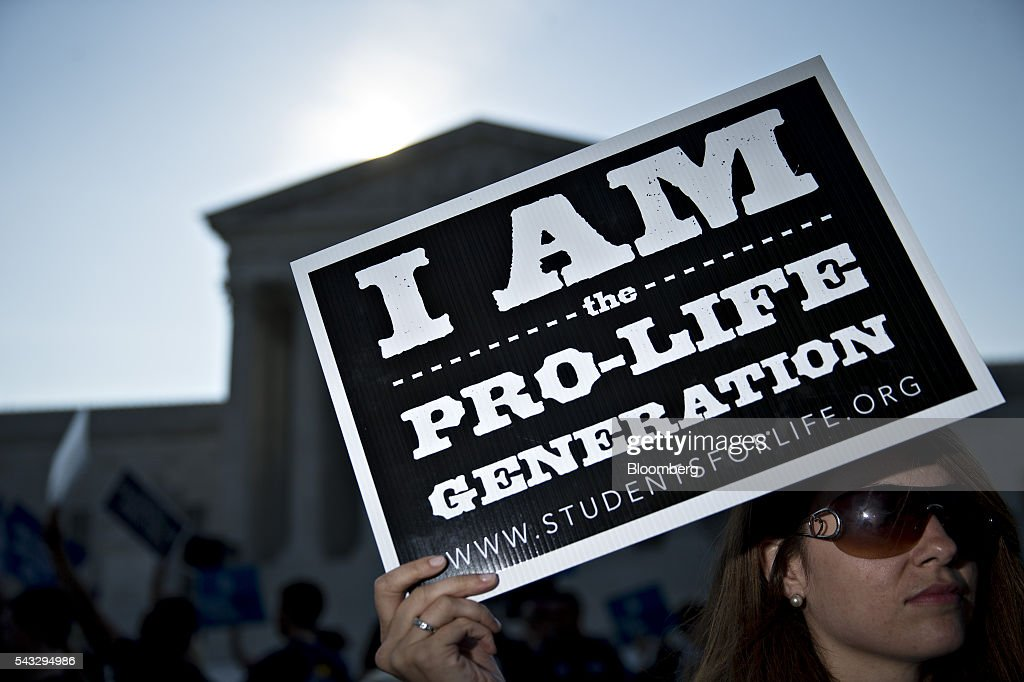 A pro-life advocate holds a sign outside the U.S. Supreme Court before rulings in Washington, D.C., U.S., on Monday, June 27, 2016. A divided U.S. Supreme Court struck down a Texas law that had threatened to close three-quarters of the states abortion clinics by putting new requirements on facilities and doctors. Photographer: Andrew Harrer/Bloomberg via Getty Images