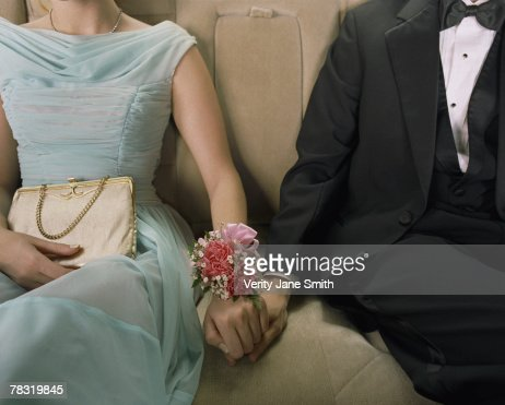 Prom couple holding hands in back seat of car
