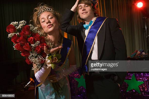 Prom king and queen gesturing together