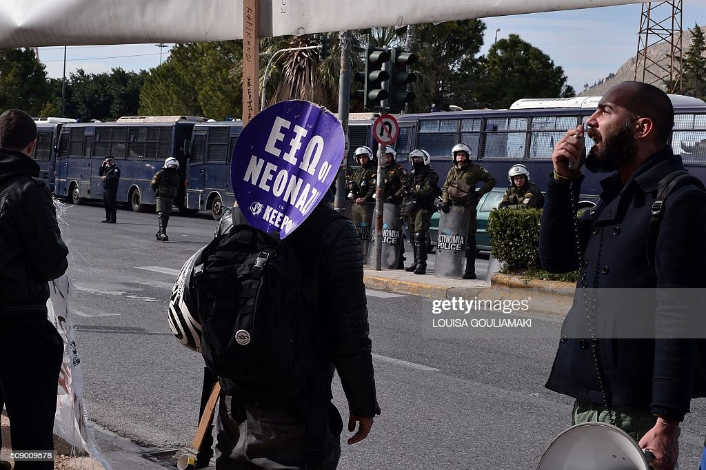 Pro-migrant protesters chant slogans during a counter-demonstration against a far-right rally on the construction of a new transit camp for refugees and migrants near the port of Piraeus in Athens area on February 8, 2016. Dozens of Greek riot police have been deployed for rally organized by the far right Golden Dawn party against plans to build a new transit camp as pro-migrants groups staged a counter-demonstration near the site. / AFP / LOUISA GOULIAMAKI